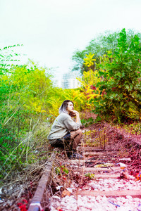 Young beautiful caucasian purple grey hair woman outdoor in the city sitting on abandoned railway, looking at camera - serious, pensive, thinking future concept
