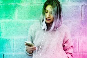 Young beautiful caucasian purple grey hair woman outdoor in the city using smart phone hand hold and headphones around her neck - technology, social network, communication concept