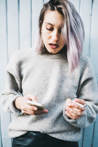 Young beautiful caucasian purple grey hair woman outdoor in the city using smart phone hand hold leaning against wall smoking a cigarette - technology, social network, communication concept