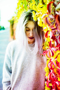 Young beautiful caucasian purple grey hair woman outdoor in the city with autumn leaves, looking down, pensive - thoughtful, serious, melancholic concept