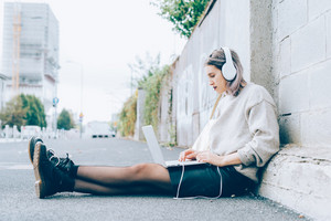 Young beautiful caucasian purple grey hair woman sitting on the ground using computer listening music with headphones - business, music, technology concept