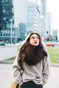 Young beautiful caucasian purple grey hair woman walking outdoor in the city wearing big scarf and glasses - hipster, cold, pensive concept