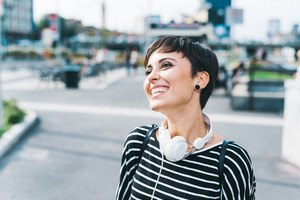 Young beautiful caucasian short brown hair woman outdoor in the city smiling with headphones around neck - serene, carefree, music concept