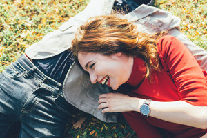 Young beautiful caucasian woman lying on the grass leaning on the belly of an unrecognizable man, laughing - love, having fun, carefree concept