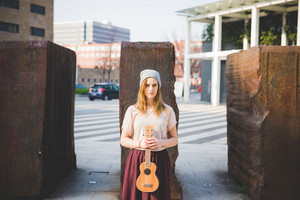 Young beautiful caucasian woman outdoor holding ukulele looking at camera - musician, artist, guitarist concept