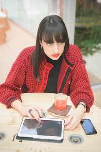 Young beautiful caucasian woman seated on a bar using a tablet, drinking a juice - communication, technology, social network concept