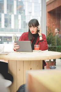 Young beautiful caucasian woman seated on a bar using a tablet talking at smartphone, drinking a juice - communication, technology, social network concept