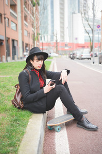 Young beautiful caucasian woman seated on a sidewalk using a smartphone looking downward - technology, social network, communication concept