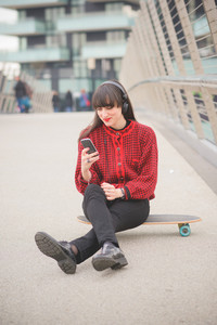 Young beautiful caucasian woman seated on a skate using a smartphone listening to music looking the screen - technology, social network, communication concept