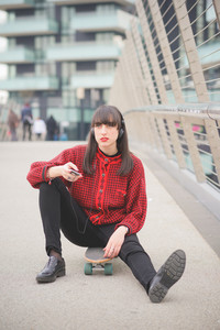 Young beautiful caucasian woman seated on a skate using a smartphone listening to music overlooking - technology, social network, communication concept