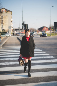 Young beautiful caucasian woman walking outdoor in the city crossing crosswalk - business, strolling concept