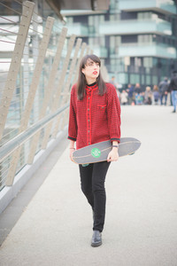 Young beautiful caucasian woman walking through the streets of the city with a skateboard posing and overlooking - youth, freshness, carefree concept