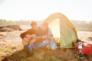 Young beautiful couple having good time with guitar near camping tent