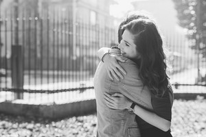 Young beautiful couple in love romantic hugging outdoor int he city back light, smiling - love, relationship, interaction concept. Black and white.