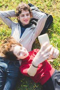 Young beautiful couple in love taking selfie outdoor in the city with smart phone hand hold - vanity, sharing, social network concept