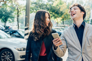 Young beautiful couple in love using smart phone together outdoor in the city - interaction, love, technology concept