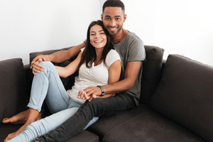 Young beautiful couple laughing on a sofa at home. Looking at camera.
