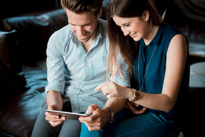 young beautiful couple lovers at the cafe using tablet