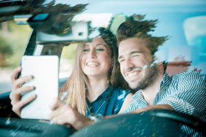 young beautiful couple lovers using tablet in the car travel