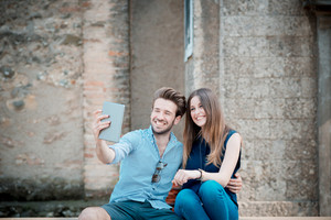 young beautiful couple lovers using tablet outdoors