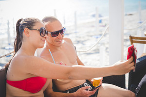 young beautiful couple man and woman taking selfie at the beach bar in summertime