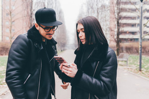 Young beautiful couple outdoor in the city using smart phone - technology, love, social network concept