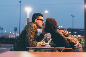 Young beautiful couple sitting outdoor in the night kissing - kiss, love, relationship concept