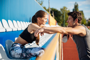 Young beautiful couple standing and talking on athletics track field