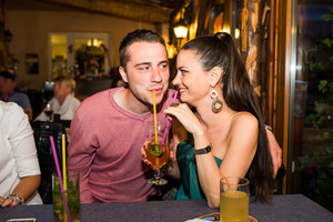 Young beautiful couple with cocktails in bar or club having fun