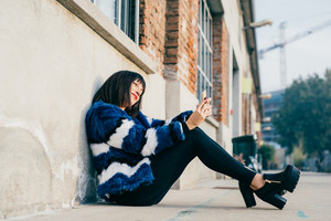 Young beautiful eastern black hair woman sitting on the floor, holding a smart phone looking down and tapping screen - technology, social network, communication concept