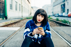 Young beautiful eastern black hair woman sitting on the floor, holding a smart phone, looking in camera pensive - technology, social network, communication concept