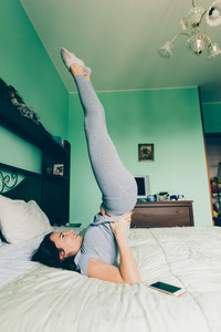 Young beautiful eastern woman doing gymnastic on bed indoor in apartment - relaxing, meditation, quiet concept