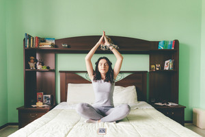 Young beautiful eastern woman doing yoga on bed indoor in apartment - relaxing, meditation, quiet concept