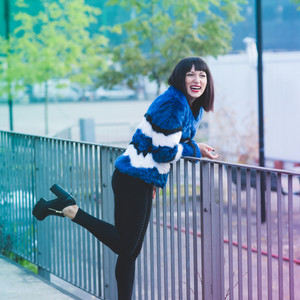 Young beautiful eastern woman leaning on a handrail, looking over laughing - happines, laughing, having fun concept.