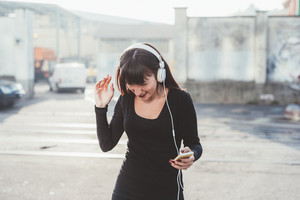 young beautiful eastern woman listening music with headphones and smart phone hand hold dancing outdoor in the city backlight, smiling - happiness, dancing, music concept