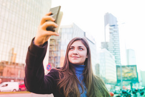 Young beautiful eastern woman outdoor in the city taking selfie using smart phone - vanity, social network, communication concept
