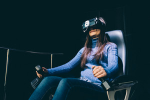 Young beautiful eastern woman sitting on a gaming chair testing augmented reality with 3D viewer - games, futuristic, augmented reality concept