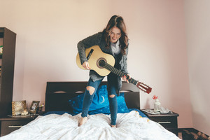 Young beautiful eastern woman standing on her bed playing guitar - girl power, music, having fun concept
