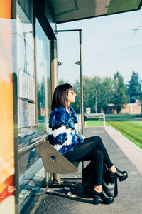 Young beautiful eastern young woman sitting at the bus stop waiting overlooking - transport, commuter concept