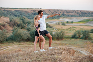 Young beautiful fitness couple standing on a hill and looking at something