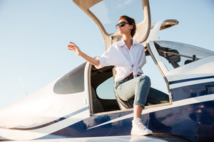 Young beautiful girl going out from the airplane after landing