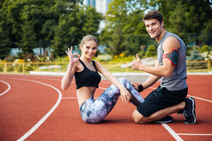 Young beautiful happy couple doing sports exercises at the stadium , showing okay and thumbs up gesture