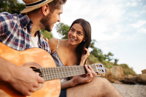 Young beautiful happy couple playing guitar while sitting at the beach