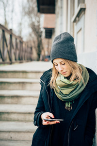 young beautiful hipster sporty blonde woman in town using smartphone