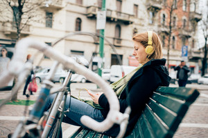 young beautiful hipster sporty blonde woman in town with bike and headphones
