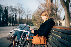 young beautiful hipster sporty blonde woman in town with bike using smartphone sitting in a bench