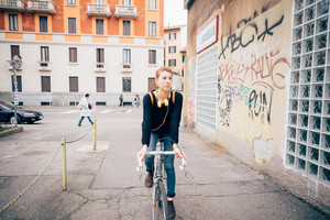 young beautiful hipster sporty blonde woman in town with bike