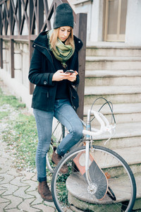 young beautiful hipster sporty blonde woman in town with skate and bike using smartphone