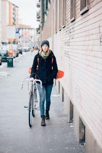 young beautiful hipster sporty blonde woman in town with skate and bike