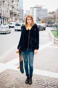 young beautiful hipster sporty blonde woman in town with skate and headphones